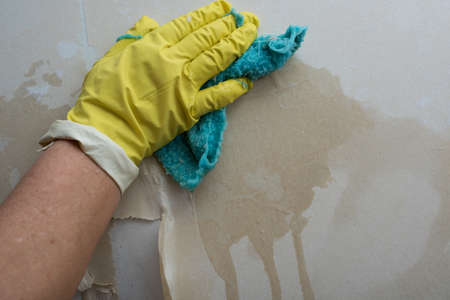 Preparing the wall for painting or sticking new wallpaper. Man in yellow gloves with a scraper in the process of removing old wallpaper. wetted with a special solution surface, yellow rag, rags.