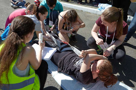 St. Petersburg, Russia - May 12, 2018: contest / exercises on first aid at the pre-hospital stage. A group of participants assists a girl who received a stab-cut leg injury.