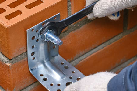 Red hollow brick. Brickwork. Installation of a chemical anchor using a special tool - resin, sleeve and metal angle. Technological stage of installation of adhesive anchor in solid hollow material.