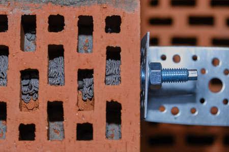 Roter Hohlziegel. Mauerwerk. Installation eines chemischen Ankers mit einem Spezialwerkzeug - Harz, Hülse und Metallwinkel. Technologischer Schritt der Installation von Klebeankern in massivem Hohlmaterial.