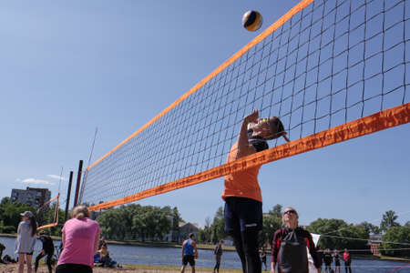 St. Petersburg, Russia-June 30, 2019: On the banks of the northern river in the city park of Europe, young people compete in volleyball. Tense moment.