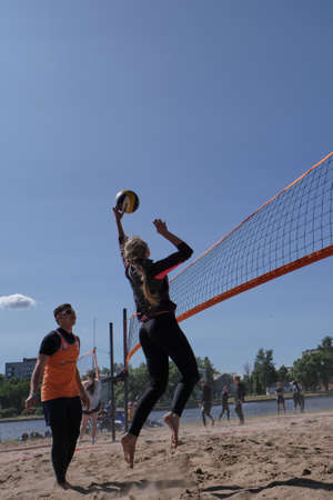 St. Petersburg, Russia- June 30, 2019: Beach volleyball sports. Young handsome man kicks the ball. City holiday. Sunny day. Editöryel