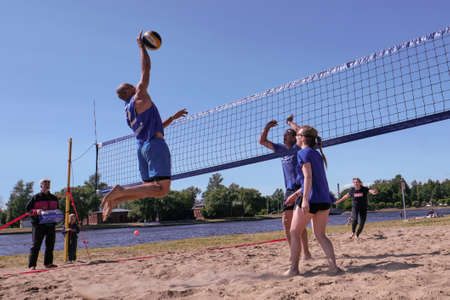 St. Petersburg, Russia-June 30, 2019: Sunny day on the shore of a European small river on the sand of the beach, young people play volleyball. Ball feed. Editöryel