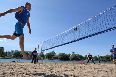 St. Petersburg, Russia-June 30, 2019: Athletic young guys playing beach volleyball. An interesting game moment. Blue sky. Bright sunny day.