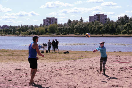 St. Petersburg, Russia-June 30, 2019: Young guys compete in beach volleyball at a city festival. Sunny clear day.