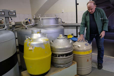 St. Petersburg, Russia - April 23, 2019: A research center employee tests canisters with liquid nitrogen. Large containers for storing biomaterials and plant breeding seeds.