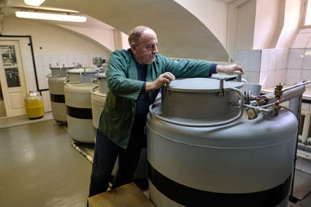 St. Petersburg, Russia - April 23, 2019: A cryobank specialist opens a tank where biomaterials are stored at ultra low temperatures.
