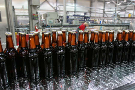 St. Petersburg, Russia - June 21, 2006: Production line of the brewery. The conveyor controller selectively checks the quality of the dark beer bottles. Middle-aged woman