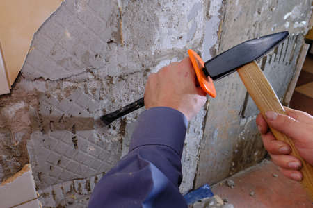 Removing old tiles from the wall in the kitchen using a chisel with a special plastic nozzle for safety when hammering. Do it yourself apartment repair. Construction garbage. Hand tool Zdjęcie Seryjne