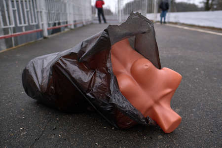 Conceptual photo - a mannequin body in a black plastic bag lies on the road. Expression and metaphor of abandonment, crime, violence. Against the background of figures of passers-by in the blur