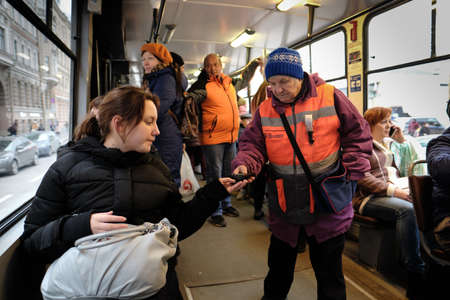 St. Petersburg, Russia - December 12, 2019: The conductor-inspector checks the availability of a ticket and payment for travel in the tram - public transport with a young attractive girl - a passenger