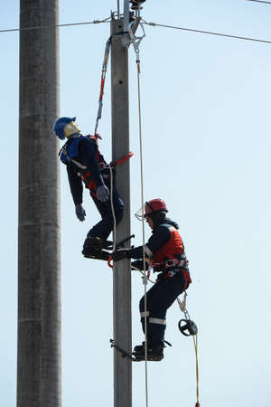 St. Petersburg, Russia - July 21, 2019: two electricians at a training exercise to rescue an injured colleague. The role of a specialist affected by current is performed by a mannequin. Post with high voltage wires