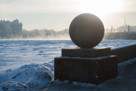 A granite ball on the embankment of the Neva River in the center of St. Petersburg in Russia. Favorite place for tourists from all over the world. Unusual climatic state of the atmosphere. Steam above the surface of the river