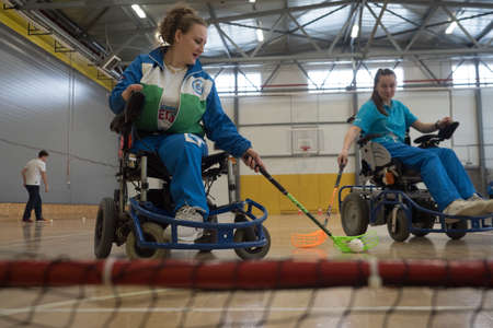 St. Petersburg, Russia - February 9, 2019: Young female sportswomen in wheelchairs prepare for competitions in the gym. Optimism, cheerfulness, stamina, excitement, the moment of the game