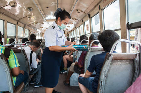 Bangkok, Thailand - March 20, 2014: A woman inspector, wearing a gauze protective mask, checks public transport tickets for passengers on a social bus