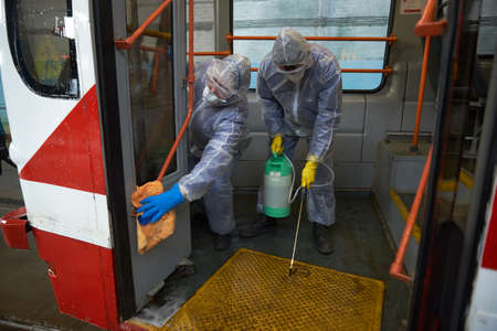 St. Petersburg, Russia - March 19, 2020: Disinfection of public transport as a preventive measure against the COVID-19 pandemic. Employees in special protective overalls handle the interior of tram