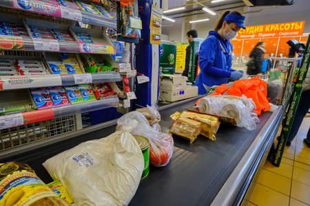 St. Petersburg, Russia - April 10, 2020: Supermarket cashier serves customers during a pandemic. Cash machine. Sales receipt. Shipping tape. Product
