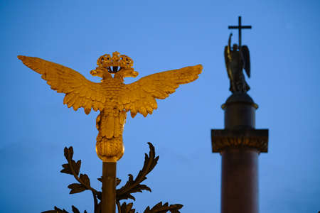 Russia, St.Peterburg. Golden double-headed eagles on the main forged gate of the State Hermitage Museum against the background of the evening sky and an angel with a cross on the Alexander Pillar