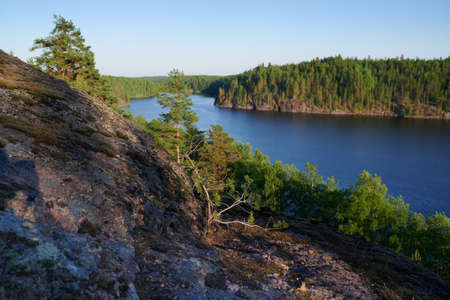 Beautiful landscape view of the Saymensky canal. Navigable canal between Lake Saimaa in Finland and Vyborg Bay in Russia. Point shooting squirrel rocks. Smooth water surface. Afternoon in the late