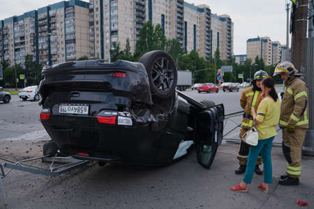 Saint Petersburg, Russia - July 21, 2020: Cherokee SUV jeep inverted after a severe road collision in the city. Firefighters eliminate gas tank explosion threat