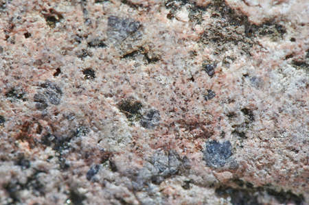 The surface of the chipped granite stone, rough, unpolished with multicolored splashes, natural, not treated, as a background for design work. Slightly discolored, horizontal, selective sharpness