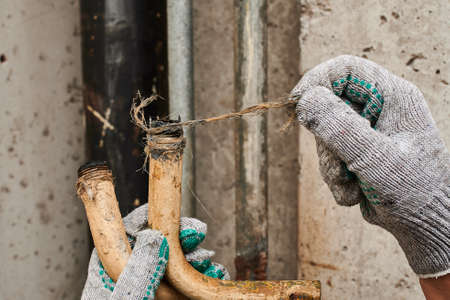 Two pieces of an old rusty bent plumbing pipe that has become unusable due to corrosion, a plumber in work gloves shows the time in the process of being replaced with modern communications Stockfoto