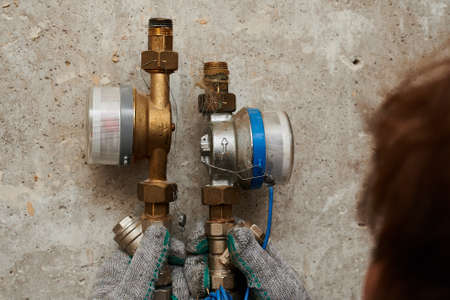 Saint Petersburg, Russia - July 30, 2020: The process of replacing the cold and hot water meter due to the failure of the flow control device. Close-up of old equipment