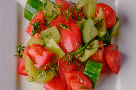 Sample of a simple salad of cucumber, tomato and pepper on a white square glossy plate. Take-away dish, on a cloth tablecloth, as a symbol of healthy eating and vegetarianism