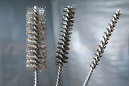 Metal brushes for cleaning holes in brick, stone and concrete before installing chemical anchors and other fasteners used in building structures. Hand tool. Against the background of the wall Stockfoto