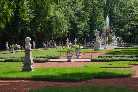 Saint Petersburg, Russia - July 27, 2020: View of the Summer Garden park opened after the Covid-19 pandemic in the city center, the main fountain with many sculptures, visitors and tourists on the alley
