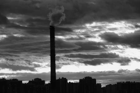 Silhouette of multi-storey buildings and heating pipes against the background of a dark cloudy sky late in the evening, in the last minutes of sunset