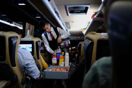 Istanbul, Turkey - October 29, 2017: A serviceman in an intercity bus offers passengers refreshing drinks and light snacks. Night flight between major cities. Selective sharpness, blur, dim lighting