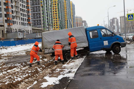 St. Petersburg, Russia - March 16, 2020: Construction workers are trying to push out a stuck Gazel truck. Spring, slush, mud, curb. Orange overalls