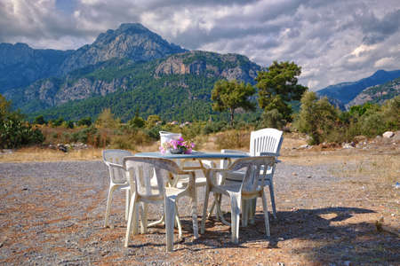 White plastic table with chairs against the backdrop of mountains in Antalya province of Goynuk. Field multi-colored flowers. Haze, green trees, horizon, landscape, beautiful background