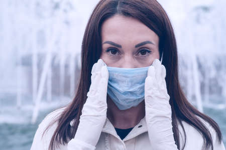 45-50-year-old brunette woman wearing a surgical protective mask to prevent coronavirus-causing Covid-19 disease. Close-up portrait, expressive eyes, makeup, elastic rubber gloves