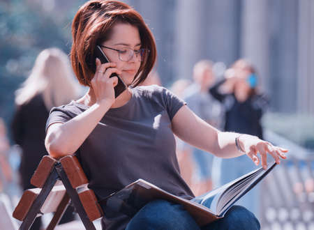 A young brunette girl wearing glasses, in a gray T-shirt with a bob haircut, brown hair color sits on a bench, on the street, talking on the phone and examines a large illustrated book Stock fotó