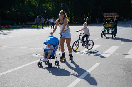 Saint Petersburg, Russia - August 18, 2020: A girl on roller skates rides with a child in a baby carriage in Victory Park on a summer sunny day on a bicycle path on the central alley