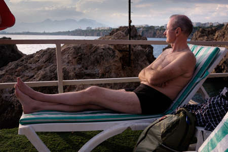 An elderly bald man with glasses lies on a sun lounger and sunbathes on the seashore in Antalya Turkey among the rocks.