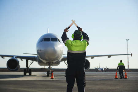 The runway traffic controller uses gestures and sticks to help the aircraft choose the correct trajectory around the airfield. Wearing a reflective vest Stock fotó