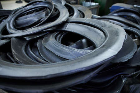 Automobile tires turned inside out, as industrial raw materials for processing at a rubber goods plant in a large bulk. The first stage in the technological cycle
