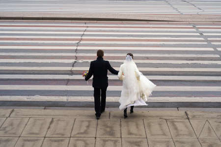 Conceptual symbolic photography. At the crosswalk, the bride in white, the groom in black. Metaphor of the beginning, the transition from one state to another, black and white stripes in a person's life