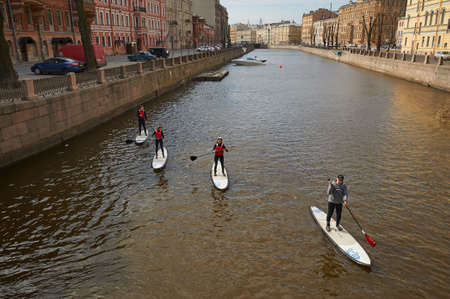 St. Petersburg, Russia - April 17, 2016: the townspeople, fans of rowing on the board while standing, on the canal in the historical center of the city