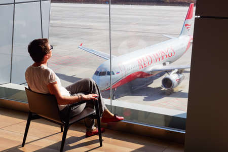 St. Petersburg, Russia - October 23, 2019: A woman in the airport lounge at a large window on a chair watches the runway. Aircraft of the RED WING company