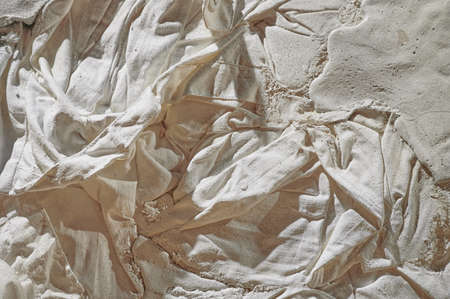 Fabric texture, soft, low-contrast, slightly toned conceptual image of white fabric prepared in plaster solution, low warm toning, specially crumpled, selective sharpness