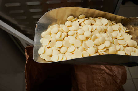 Granules of white chocolate raw materials in a metal ladle on the background of a small-scale wholesale line for the production of sweets and confectionery Standard-Bild
