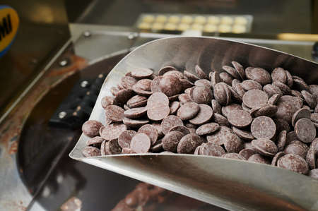 a ladle with pieces of raw chocolate in the hands of a pastry chef against the background of a production line, small-scale wholesale production of chocolates Standard-Bild