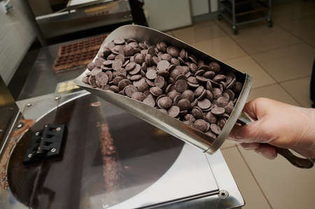 a ladle with pieces of raw chocolate in the hands of a pastry chef against the background of a production line, small-scale wholesale production of chocolates Stockfoto
