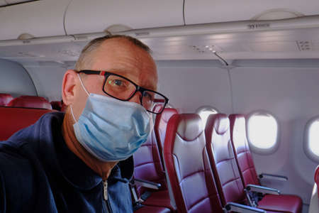 An elderly man 60-65 years old wearing a protective mask and glasses alone in the cabin of a passenger airliner. Stock fotó