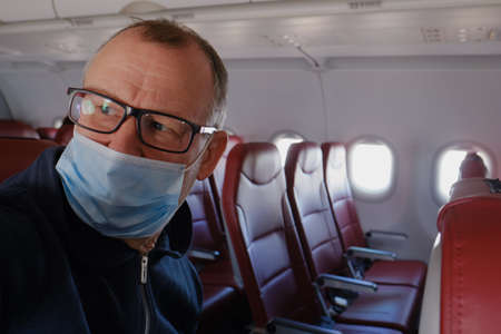 An elderly man 60-65 years old wearing a protective mask and glasses alone in the cabin of a passenger airliner. Empty seats - social distancing during the  pandemic