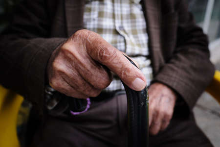 An elderly unrecognizable man sits on a chair with a stick in his hands. Wrinkled hands close up. Conceptual photography symbol about aging and old age Stockfoto